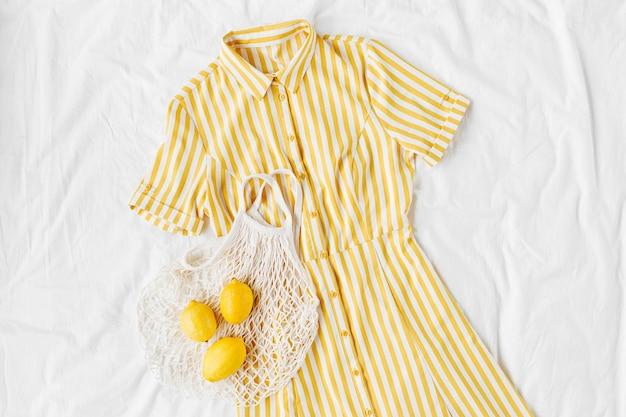 Gele jurk met strepen met eco-tas en citroenen op wit bed. stijlvolle zomeroutfit voor dames. trendy kleding. plat lag, bovenaanzicht.