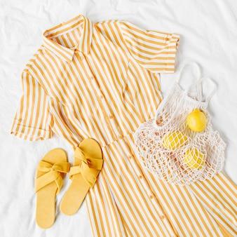 Gele jurk met strepen met eco tas en slippers op wit bed. stijlvolle zomeroutfit voor dames. trendy kleding. plat lag, bovenaanzicht.