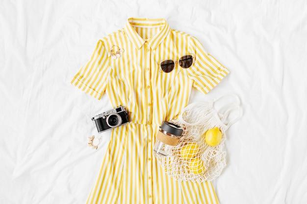 Gele jurk met strepen met eco tas, zonnebril en fotocamera op wit bed. stijlvolle zomeroutfit voor dames. trendy kleding. vakantieconcept. plat lag, bovenaanzicht.