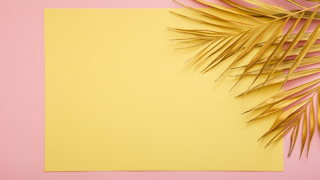 Gele kaart kopie ruimte voor tekst in frame gemaakt van gouden palmblad. tropisch palmverlof op roze achtergrond. geschilderd bladgoud op zomer bloemen achtergrond. lange webbanner met kopieerruimte.