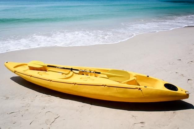 Gele kajak op het strand