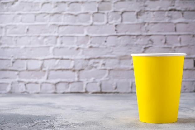 Gele kartonnen beker op een grijze tafel. kopieer ruimte