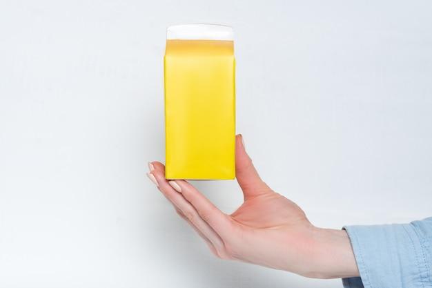 Gele kartonnen doos of verpakking van tetra pack in een vrouwelijke hand.