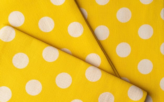 Gele katoenen stof doek textuur. polka dots textiel achtergrond of behang.