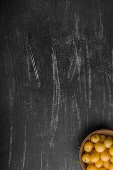 Gele kersen in een houten kom in de benedenhoek