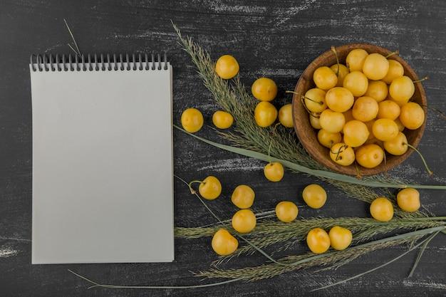 Gele kersen in een houten kom met opzij een notitieboekje
