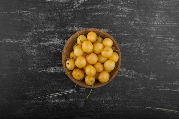 Gele kersen in een houten kom op het bord