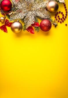 Gele kerstmisachtergrond die met spar en speelgoed wordt verfraaid