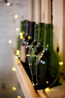 Gele kerstmisslinger en groene wijnflessen op een houten plank, verticaal