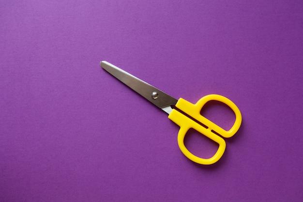 Gele kid's briefpapier rechtshandige schaar op paars