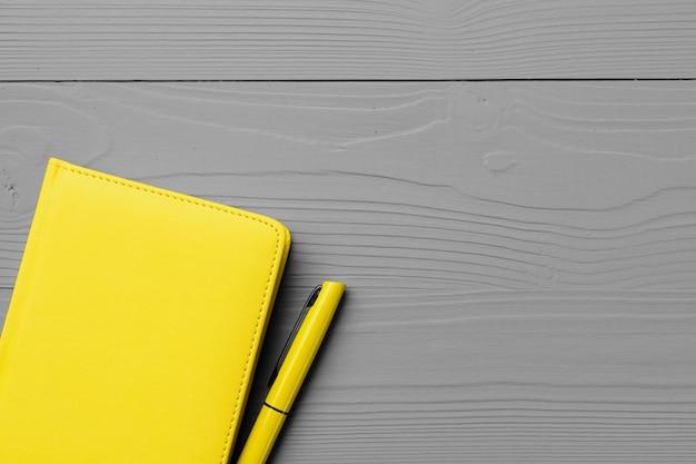Gele kladblok op grijze houten bovenaanzicht