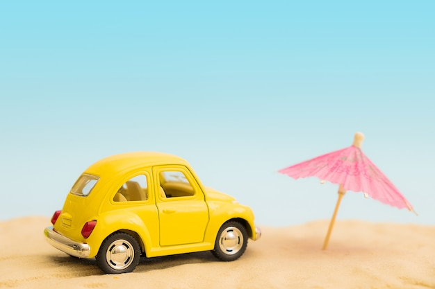 Gele kleine auto op strand en zand. vakantie concept. retro autovakantie.