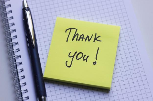 Gele kleverige nota op witte blocnote met de woorden dank u