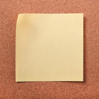 Gele kleverige post opmerking op cork board