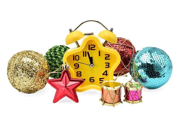 Gele klok die kerstmistijd met speelgoed op geïsoleerd wit toont
