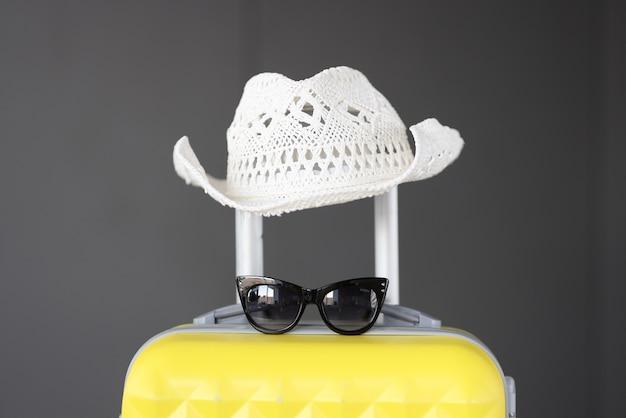 Gele koffer met witte panamahoed en zonnebril. toerisme en reizen concept