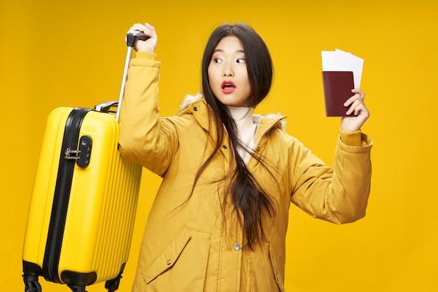 Gele koffer paspoort vliegtuigtickets verrast vrouw