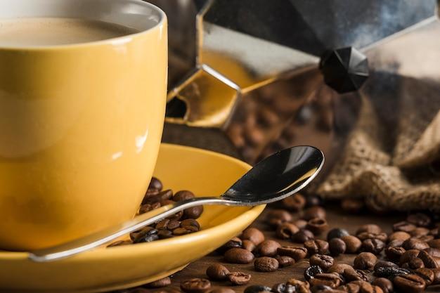 Gele koffie die dichtbij bonen en geiserkoffiezetapparaat wordt geplaatst