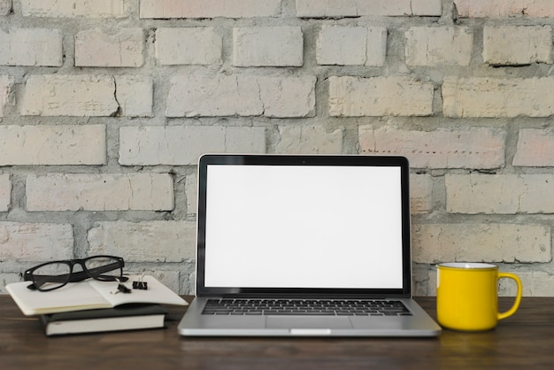 Gele koffiemok; schouwspel; opengeklapte laptop en briefpapier op houten tafel met bakstenen muur achtergrond