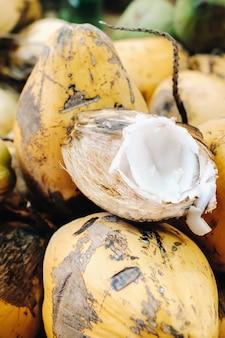 Gele kokosnoten worden verkocht op de markt van het eiland mauritius. snijd een jonge kokosnoot met makoto. veel kokosnoten op de markt.
