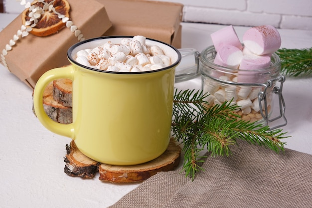 Gele kop met cacao versierd met marshmallows op een standaard gemaakt van gezaagd hout, een pot marshmallows, een sparrentak en kerstcadeaus op de achtergrond