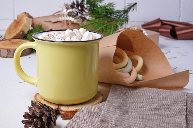Gele kop met cacao versierd met marshmallows op een standaard gemaakt van gezaagd hout, een zak met marshmallows, een sparrentak en kerstcadeaus op de achtergrond