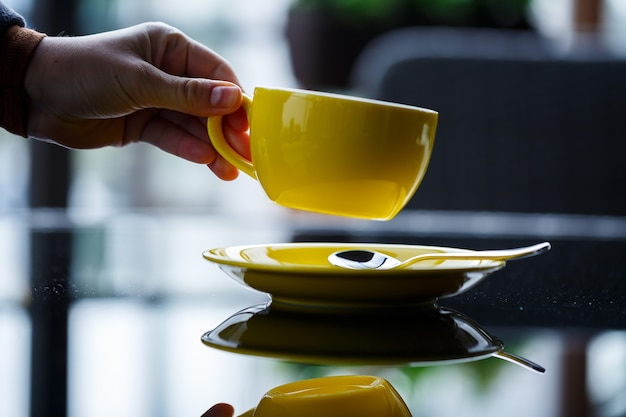 Gele kop voor koffie of thee met een schotel in de handen van een meisje op de achtergrond van een glazen tafel.