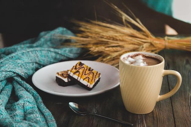 Gele kopje koffie met marshmallows en oranje dessert op een witte plaat.