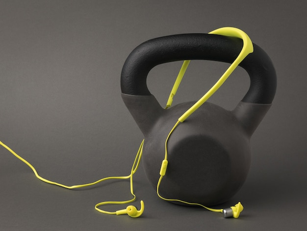 Gele koptelefoon met een draad en een sportgewicht op een donkergrijze achtergrond. sportieve levensstijl. kleuren 2021.