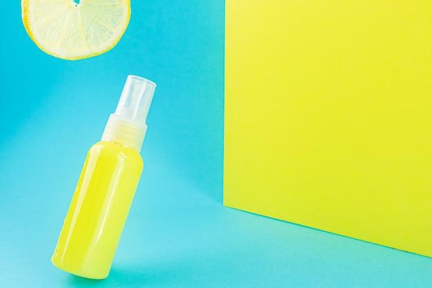Gele kosmetische fles en citroen op een blauwe ruimte. stijlvol concept van organische essences, schoonheids- en gezondheidsproducten. kopieer ruimte, minimalisme, levitatie-effect.