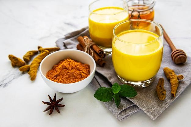 Gele kurkuma latte drank. gouden melk met kaneel, kurkuma, gember en honing op witte marmeren achtergrond.