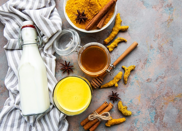 Gele kurkuma latte drank. gouden melk met kaneel, kurkuma, gember en honing over concrete achtergrond.