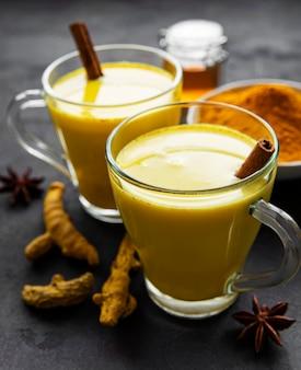 Gele kurkuma latte drank. gouden melk met kaneel, kurkuma, gember en honing over zwarte steenachtergrond.