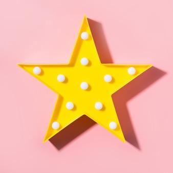 Gele lamp als ster met witte led-lampjes op roze achtergrond.