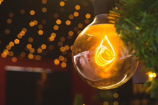 Gele lamp onder kerstboomtakken en kerstverlichting.