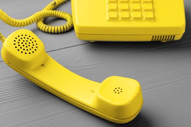 Gele .landline telefoon op grijze bovenaanzicht kopie ruimte.