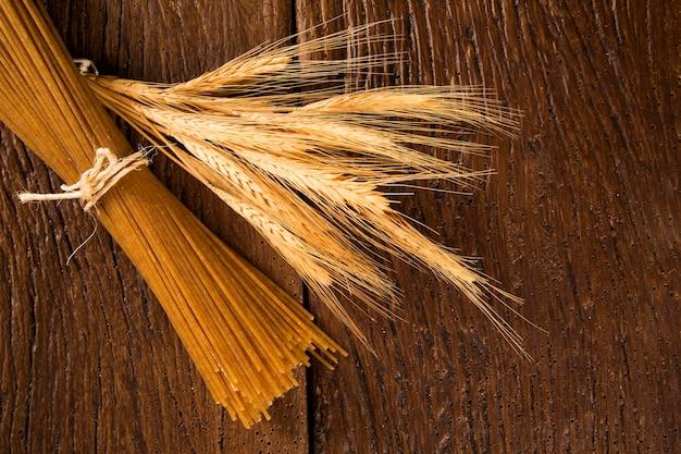 Gele lange integrale spaghetti en korenaren op een rustieke ondergrond