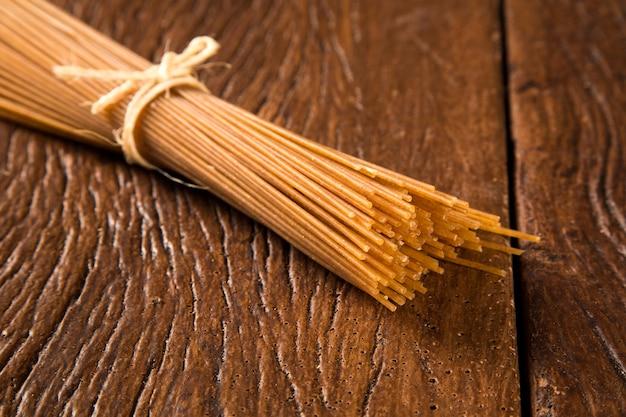 Gele lange integrale spaghetti op een rustieke ondergrond