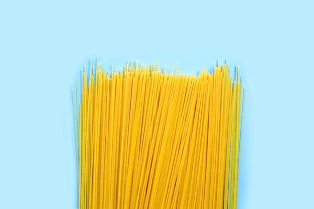 Gele lange spaghetti op blauwe ondergrond