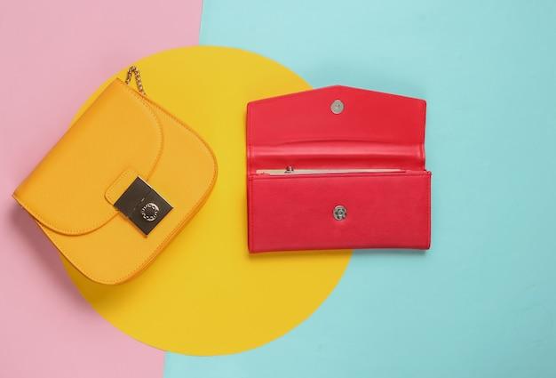 Gele leerzak en rode portefeuille op pastelkleurentafel