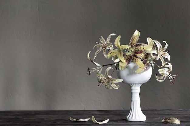Gele lelie in keramische witte vaas op houten tafel