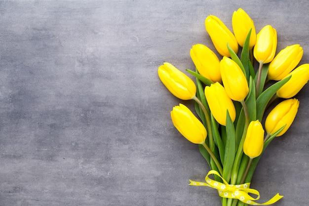 Gele lentebloemen, tulp op een grijze ondergrond.