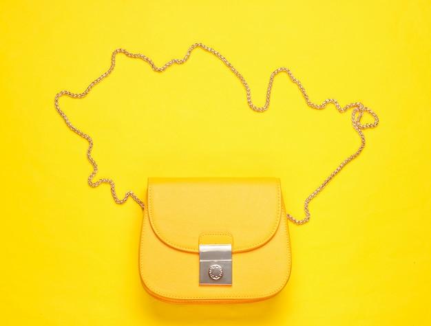 Gele leren mini tas met ketting op gele ondergrond