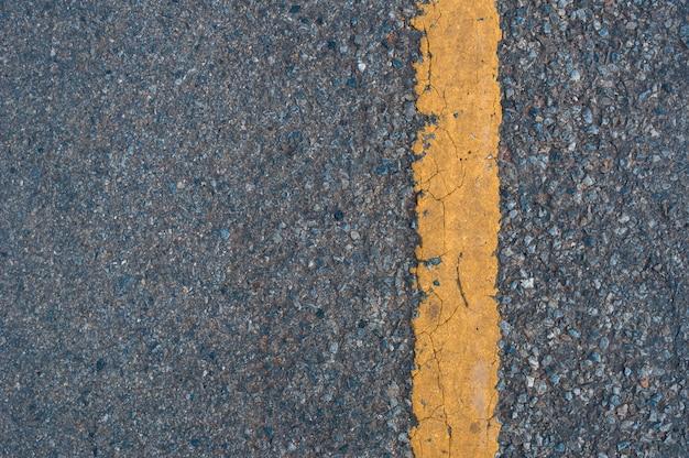 Gele lijn op de achtergrond van de wegtextuur