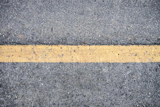 Gele lijn op de textuur van de asfaltweg