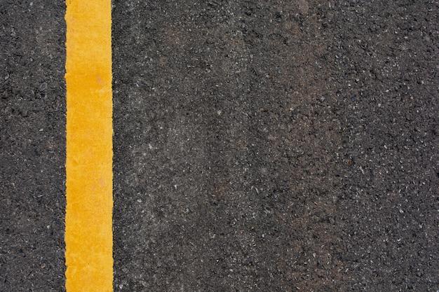 Gele lijn op de zwarte achtergrond van de asfaltweg met exemplaarruimte