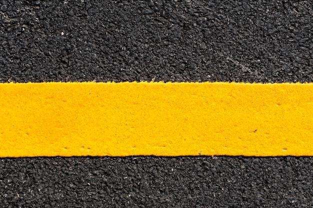 Gele lijn op nieuw asfaltdetail, straat met gele lijntextuur
