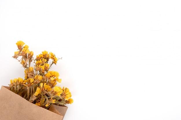 Gele limonium in een ambachtelijke verpakking op wit