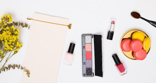 Gele limoniumbloem; gouden haarspeld; wit papier; lippenstift; nagellak flessen; make-upborstel en makarons op witte achtergrond