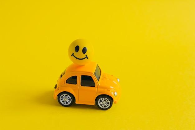 Gele machine met bal met geschilderde lachende gezicht gehecht aan het dak op geel